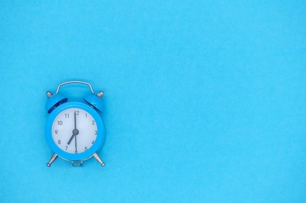 Niebieski budzik vintage ze strzałkami i dzwonkiem na niebieskim tle. puste miejsce na projekt, miejsce na tekst, pojęcie czasu