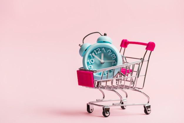 Niebieski budzik w miniaturowym wózku na zakupy