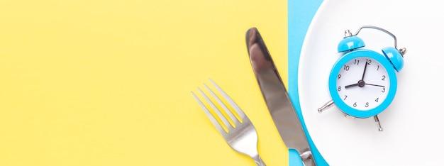 Niebieski budzik, widelec, nóż na kolorowym tle papieru. koncepcja przerywanego postu. baner poziomy - obraz