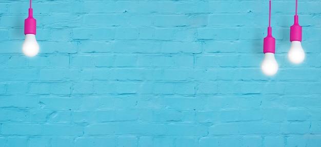 Niebieski ceglany mur z żarówkami. kreatywna kopia miejsca na tekst lub obraz. format banera