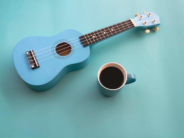 Niebieski ceramiczny kubek z czarną kawą umieszczony obok ukulele, na pastelowym tle