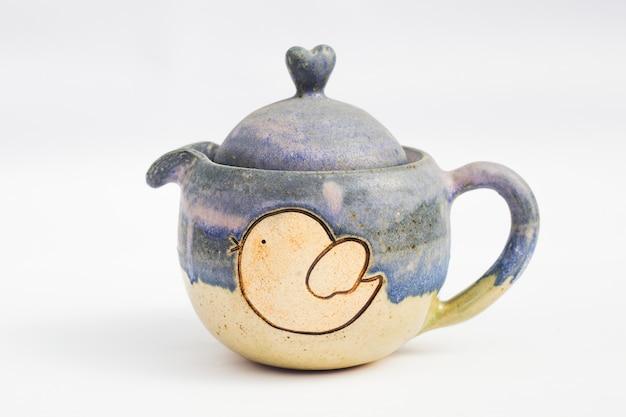 Niebieski czajniczek ceramiczny kamionkowy z białym tłem