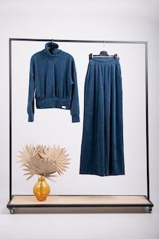 Niebieski damski garnitur z dzianiny, bluza, spodnie palazzo odzież na wieszaku. modne, nowoczesne, młodzieżowe ubrania.