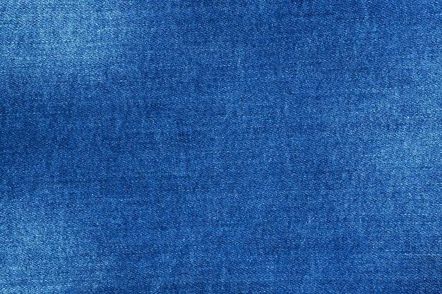 Niebieski denim o fakturze z przetarciami, stołowy materiał z dżinsów.