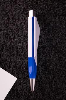 Niebieski długopis i biała karta na ciemnym tle.