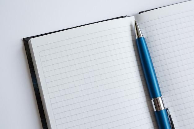 Niebieski długopis leży na białej kartce czarnego notatnika