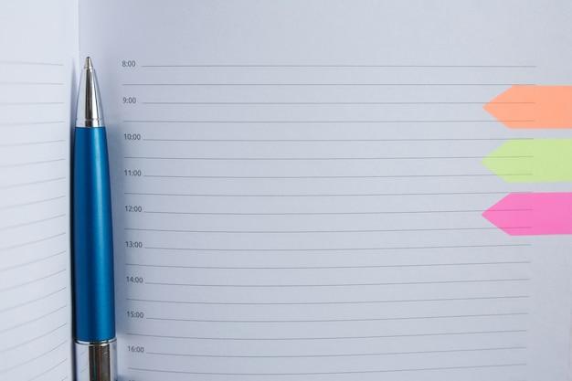 Niebieski długopis leży na białej kartce dziennika