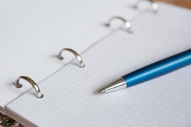 Niebieski długopis leży na białej kartce notatnika