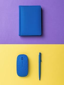 Niebieski długopis, mysz komputerowa i notatnik na dwukolorowej powierzchni. stylowe akcesoria dla biznesu i freelancerów. leżał na płasko.