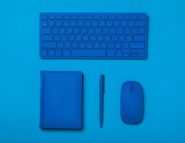 Niebieski długopis, notatnik, klawiatura i mysz na niebieskim tle. stylowe akcesoria dla biznesu i freelancerów. leżał na płasko.