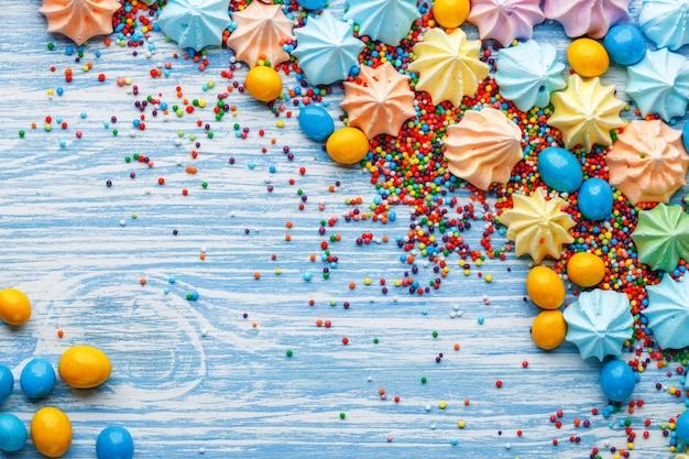 Niebieski drewniany stół pełen cukierków, lizaków, ciastek i słodkiej niezdrowej żywności