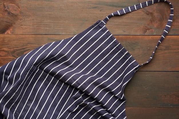 Niebieski fartuch kuchenny z materiału tekstylnego w białe paski