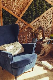 Niebieski fotel z dzianinową beżową poduszką, nowoczesne wnętrze