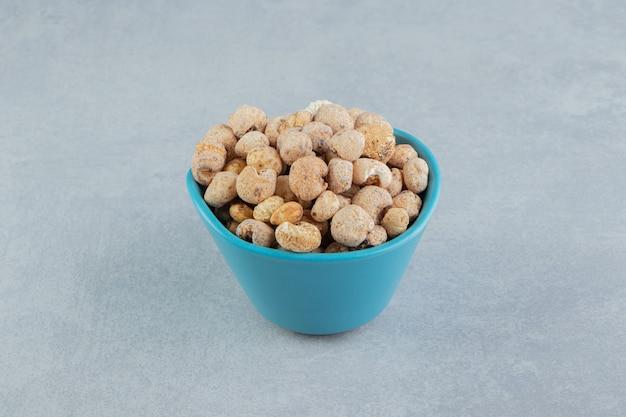 Niebieski, głęboki kubek pełen pysznych suszonych owoców.