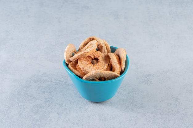 Niebieski, głęboki talerz ze zdrowymi suszonymi owocami na marmurze.