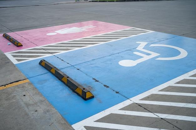 Niebieski handicap przy parkowaniu samochodu znak na zewnątrz dla wózków inwalidzkich.