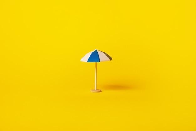 Niebieski i biały parasol plażowy na żółtym tle, koncepcja wakacje