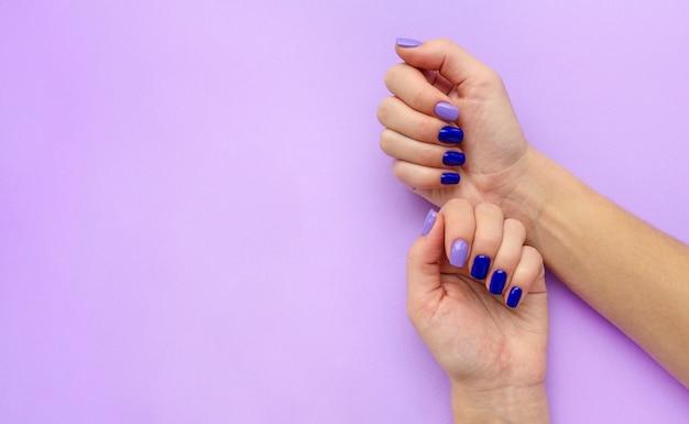 Niebieski i liliowy manicure na rękach kobiety