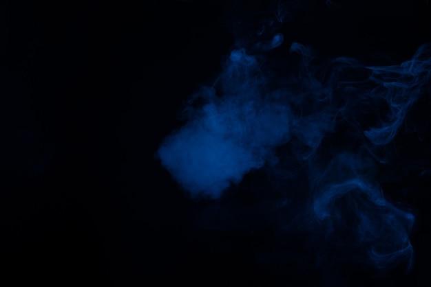 Niebieski i różowy steam na czarnym tle. skopiuj miejsce.