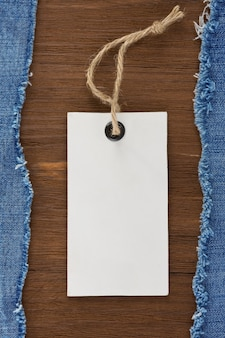 Niebieski jean i przywieszka z ceną na tle tekstury drewna