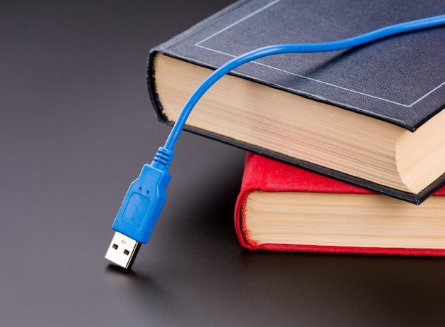 Niebieski kabel usb leży na książkach