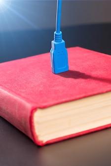 Niebieski kabel usb podłączony do czerwonej książki