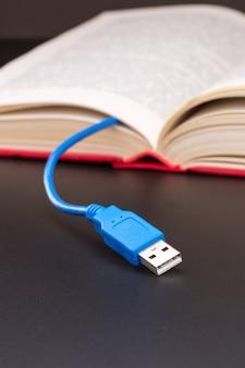 Niebieski kabel usb wystaje z czerwonej księgi. widok makro