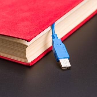 Niebieski kabel usb wystaje z czerwonej księgi. zamknąć widok
