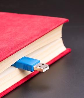 Niebieski kabel usb wystaje z czerwonej księgi, zbliżenie