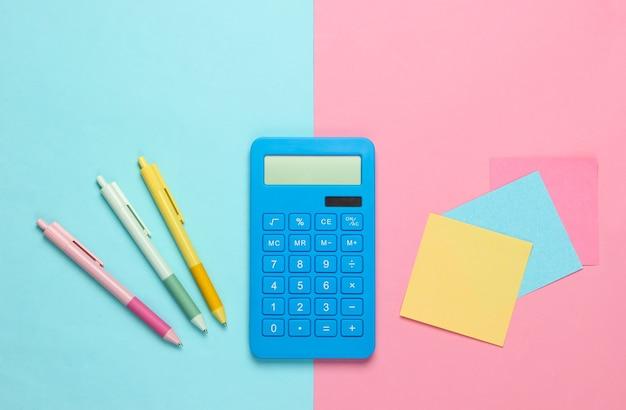 Niebieski kalkulator z długopisami i kolorowymi kartkami papieru na różowo-niebieskim. narzędzia biurowe