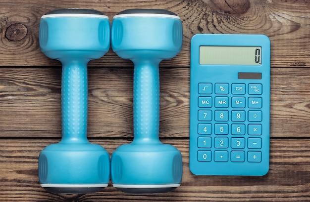 Niebieski kalkulator z hantlami na drewnianym stole