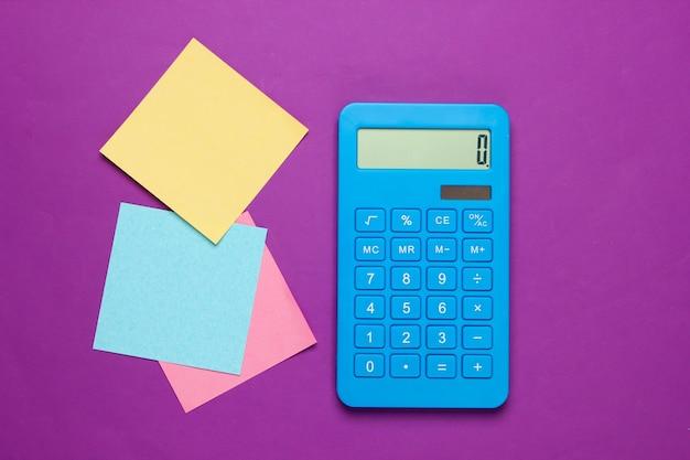 Niebieski kalkulator z kolorowymi kartkami papieru notatki na fioletowo. narzędzia biurowe