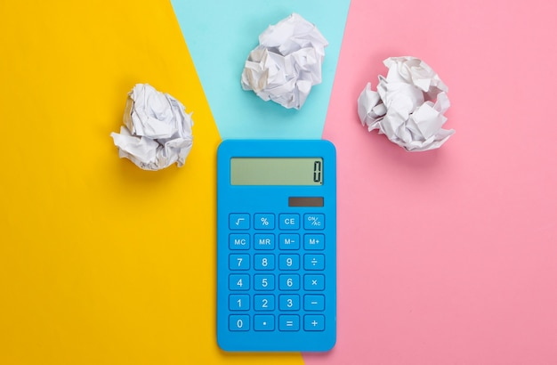 Niebieski kalkulator z pomarszczonymi kulkami papieru na kolorowym pastelowym kolorze