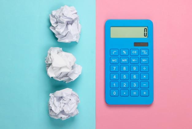 Niebieski kalkulator z pomarszczonymi kulkami papieru na niebiesko-pastelowym pastelowym kolorze