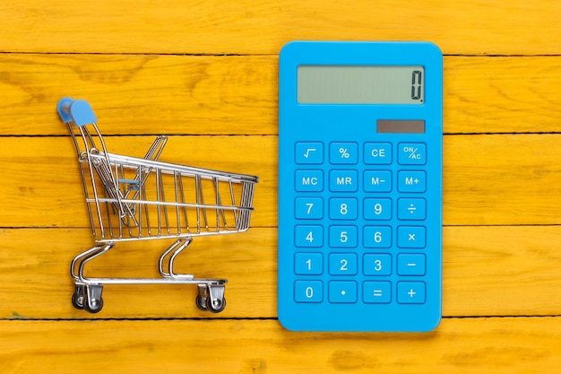 Niebieski kalkulator z wózkiem na zakupy na żółtym drewnianym pudełku
