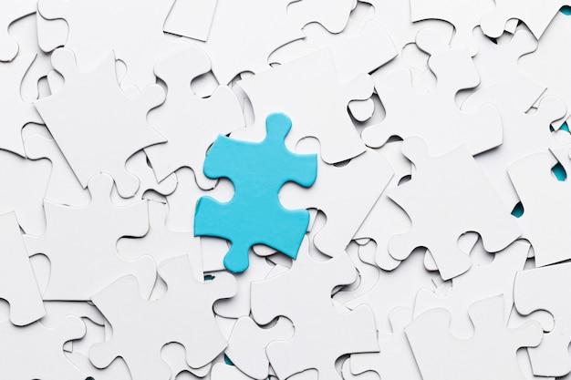 Niebieski kawałek układanki nad białymi puzzlami
