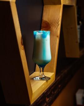 Niebieski kieliszek koktajlowy prezentowany w drewnianych półkach