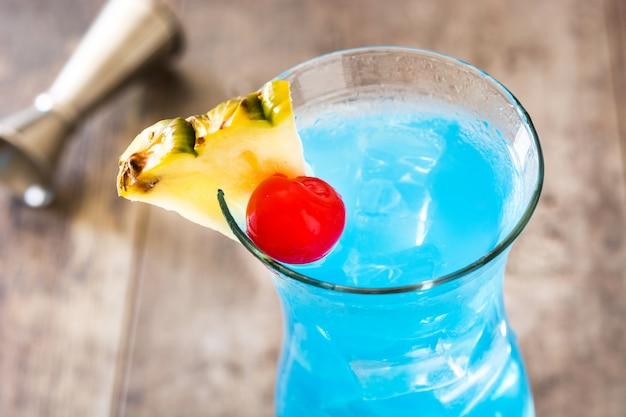Niebieski koktajl hawajski na drewnianym stole z bliska
