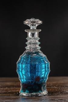Niebieski koktajl w rocznika karafki na drewnianym stole
