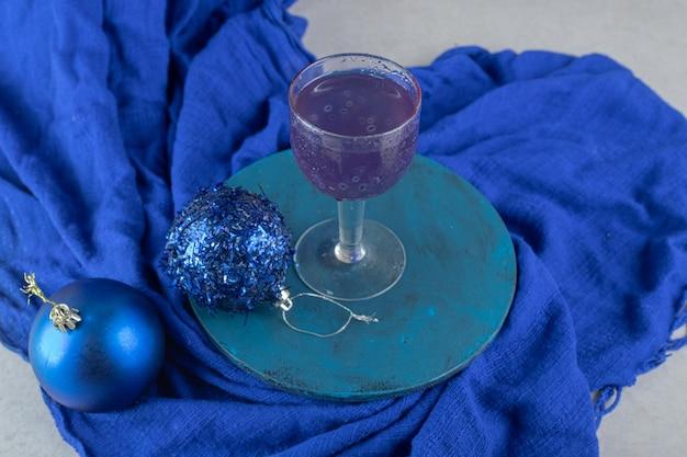Niebieski koktajl z błyszczącymi bombkami na niebieskim talerzu