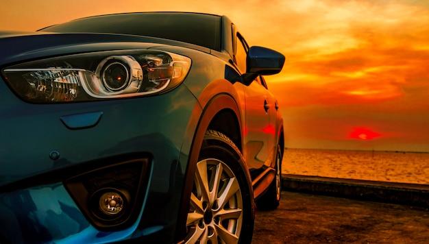 Niebieski kompaktowy samochód suv ze sportem i nowoczesnym designem zaparkowany na betonowej drodze nad morzem w su