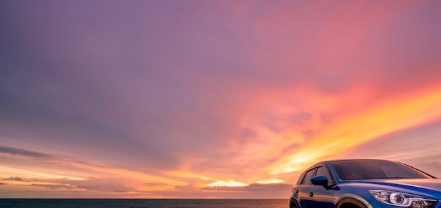 Niebieski kompaktowy suv sportowy i nowoczesny zaparkowany przy plaży o zachodzie słońca