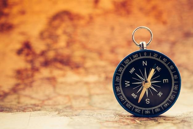 Niebieski kompas jest umieszczony na mapie świata.