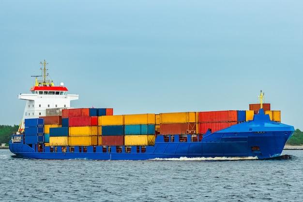 Niebieski kontenerowiec w pełni załadowany w drodze