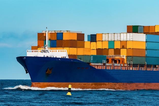 Niebieski kontenerowiec w podróży. logistyka i branża transportowa