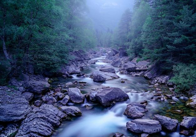 Niebieski krajobraz z rzeką i zimnym światłem zimy. nocna i mistyczna atmosfera, magiczna i nawiedzająca. ordesa pyrenees.