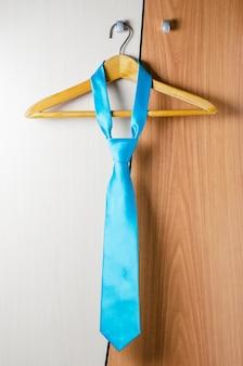 Niebieski krawat mężczyzny wisi na drzwiach szyfonu. koncepcja stylu udanego mężczyzny.