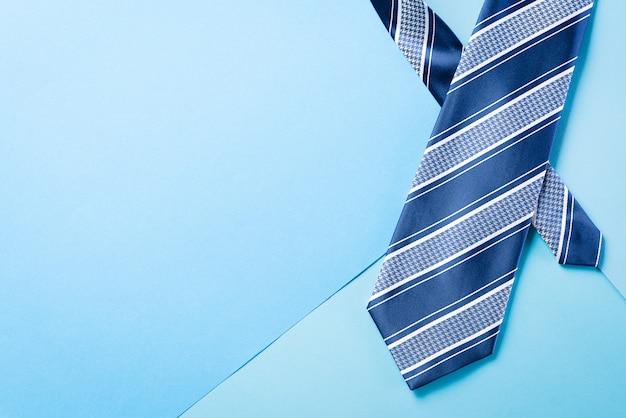 Niebieski krawat na jasnej pastelowej ścianie.