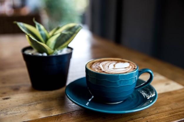 Niebieski kubek gorącego cappucino jest na tle drewniany stół. mały kwiatek jest do tego drobiazgowy.