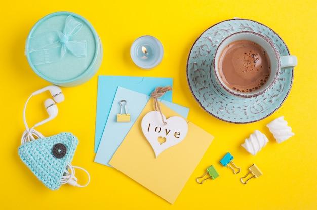 Niebieski kubek gorącej czekolady i puste notatki